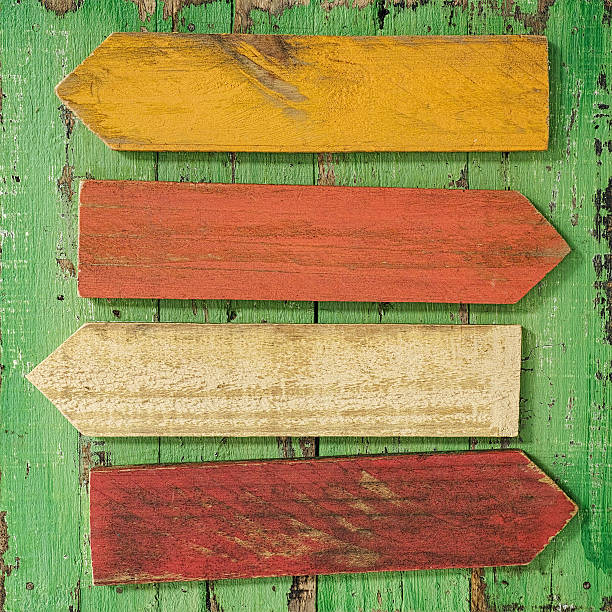 Old colourful weathered wood sign arrows. stock photo