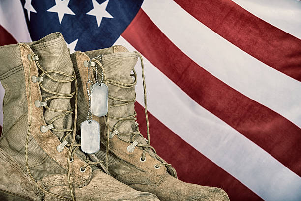 Old combat boots and dog tags with American flag stock photo