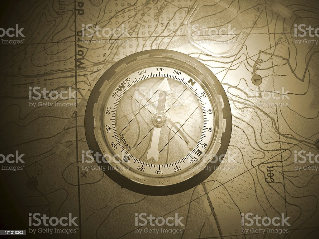 Old compass on old map pointing north-west royalty-free stock photo