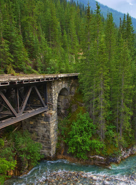 Old concrete bridge with metal structure on a river. Rocky mountain ( Canadian Rockies ). Near the city of Calgary. Portrait, fine art. Jasper and Banff National Park, Alberta, Canada: August 3, 2018 stock photo