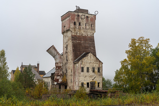 Stallberg, Sweden, 27-09-2020. Head frame at an old closed down mine in Sweden, overgrown by autumn colored trees and bushes