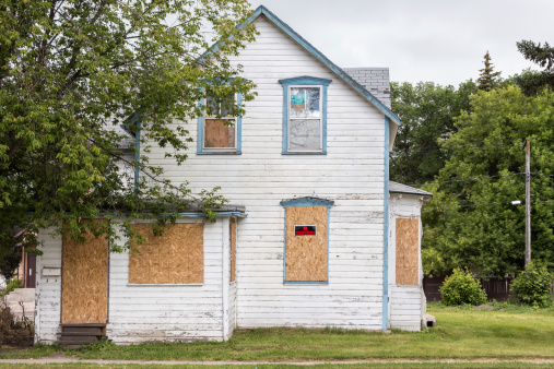 an old white condemned two-story house with windows boarded up and a sign saying
