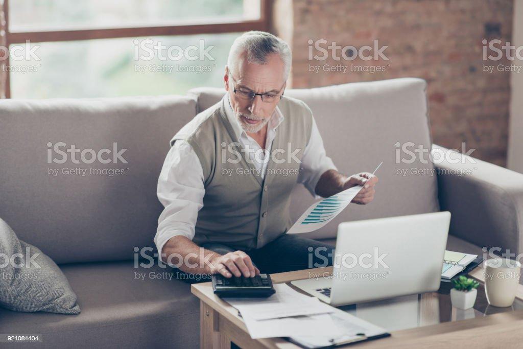 Abuelo barbudo concentrado inteligente seguro viejo es verificar sus cálculos sentado delante del monitor en la oficina - Foto de stock de Accesorio para ojos libre de derechos