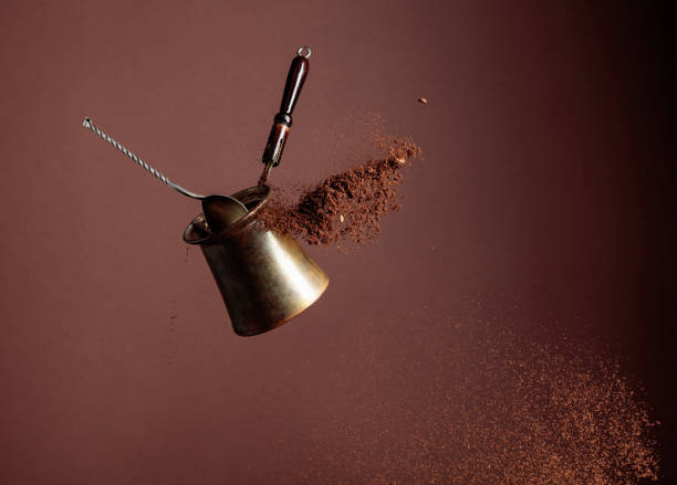 Old copper coffee maker and a spoon with ground coffee in motion. stock photo