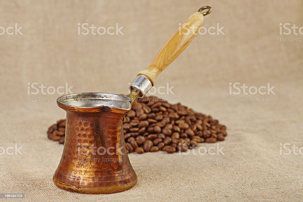 Old copper pot and coffee beans on canvas. Selective focus royalty-free stock photo