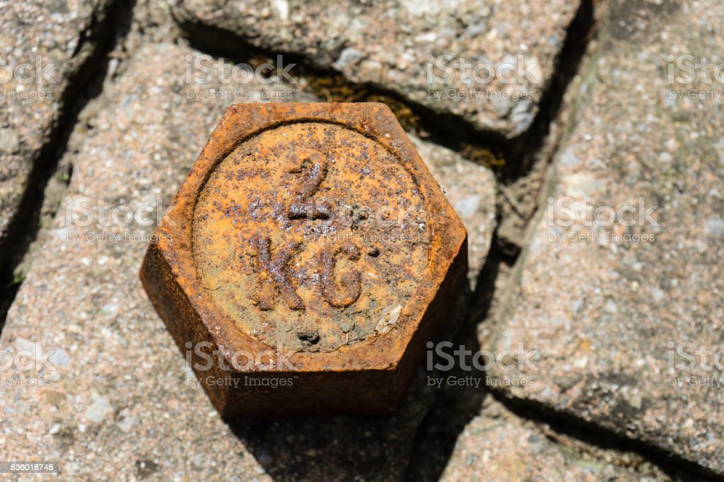 old copper weight mass on floor stock photo