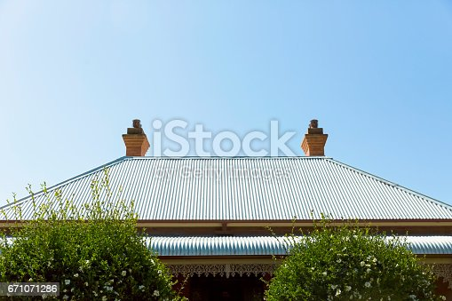 Old corrugated iron roof with chimney, blue sky background with copy space, full frame horizontal composition