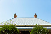 Old corrugated iron roof with chimney, sky background, copy space
