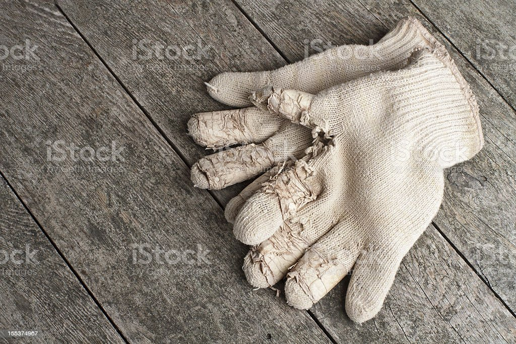 Old cotton work gloves on weathered wood. royalty-free stock photo