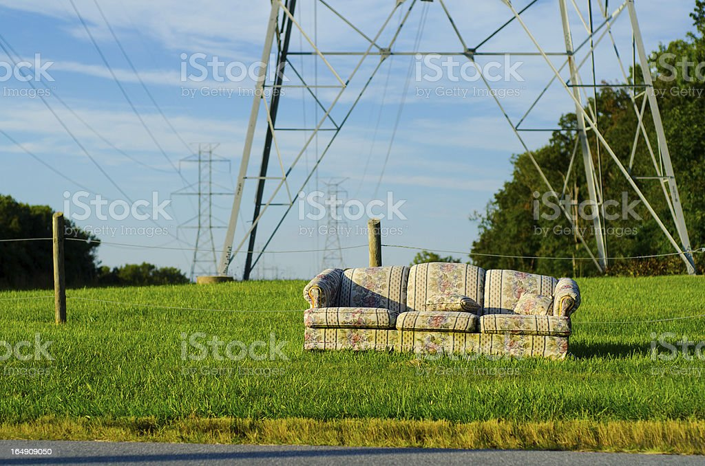 Old couch on the grass close to electric lines
