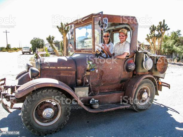 Old couple driving an old rusty car from 1915 in Chloride Nevada during day