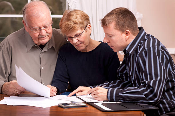 Old couple getting financial advice from young man stock photo
