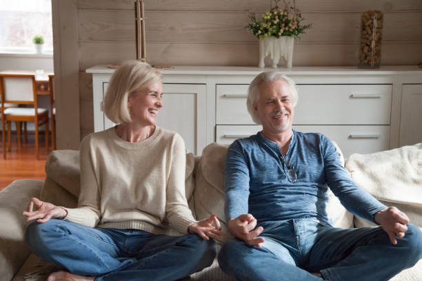 Old couple having fun laughing doing yoga together at home stock photo