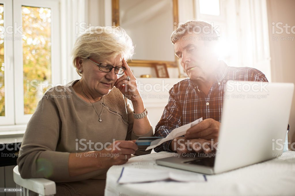Old couple having problems with their home finances. stock photo