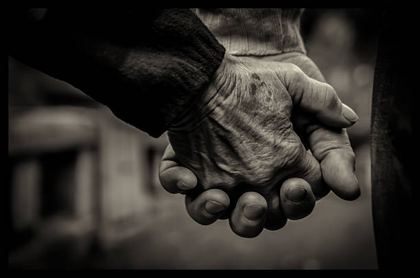 Old couple holding hands stock photo