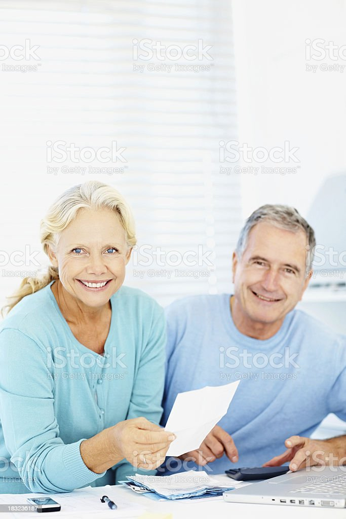 Old couple in home office with laptop and paperwork smiling royalty-free stock photo