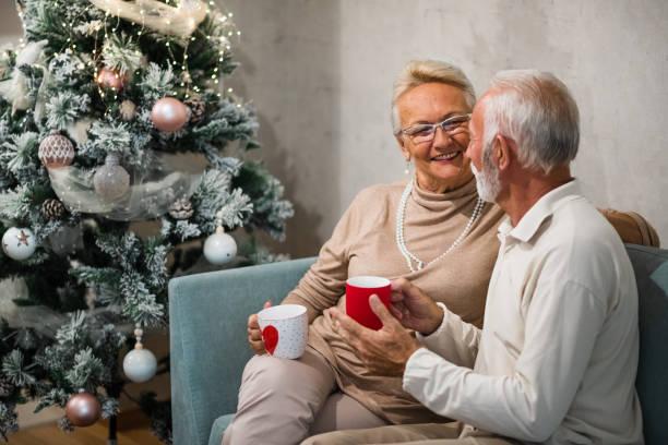 Old couple is sitting on sofa enjoying hot beverage. Christmas concept. stock photo