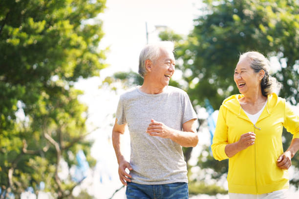 old couple jogging outdoors stock photo