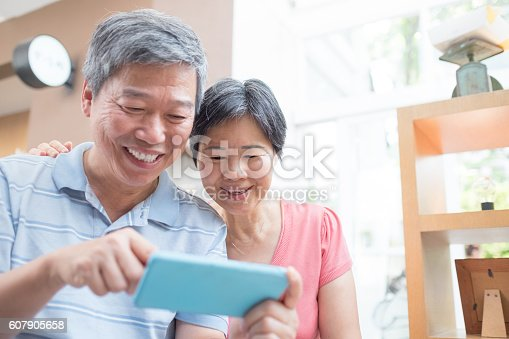 the old couple look smaprt phone happily, asian