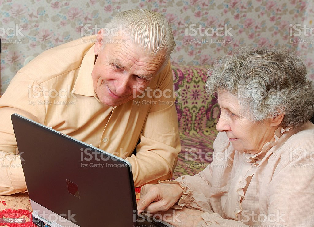 old couple look to the laptop with active interest royalty-free stock photo