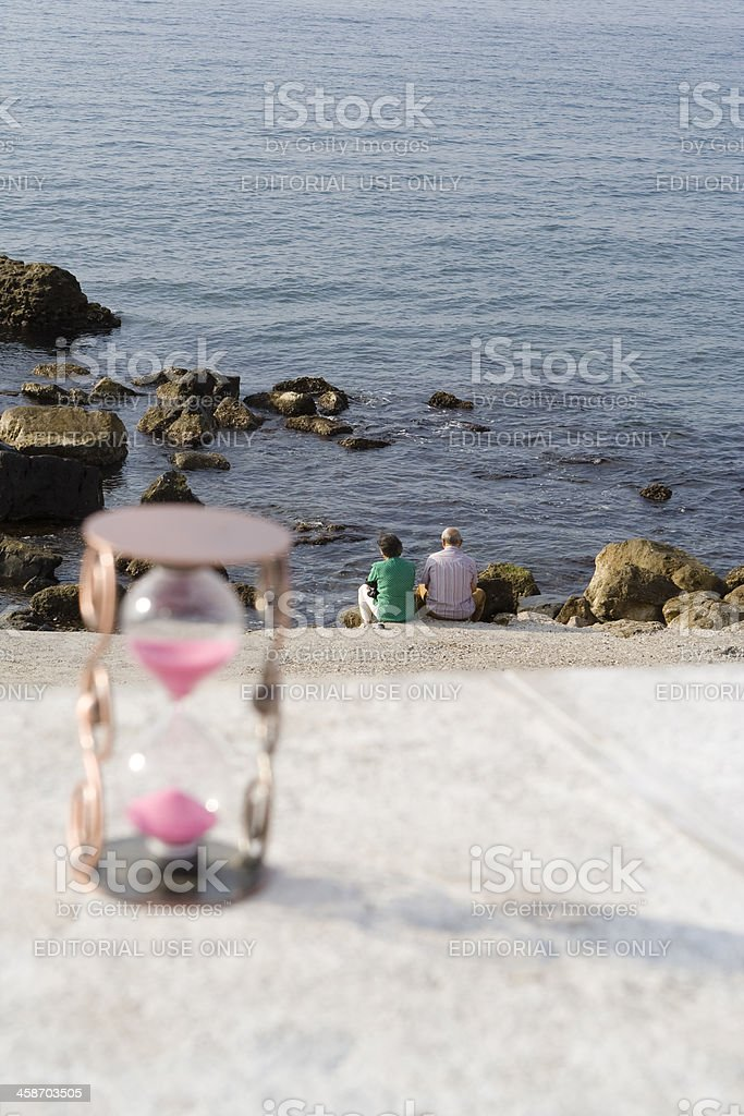 Old couple Looking at Sea with Hourglass royalty-free stock photo