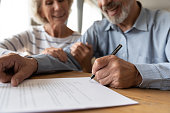 istock Old couple make agreement sign insurance contract 1211971898