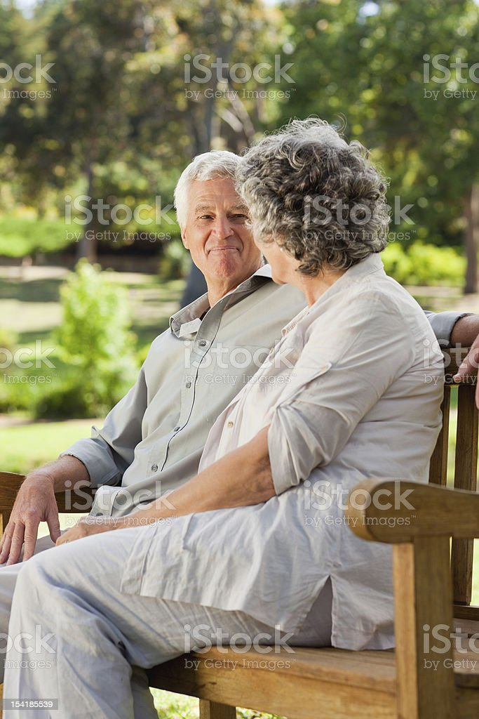 Old couple sitting down looking at each other royalty-free stock photo