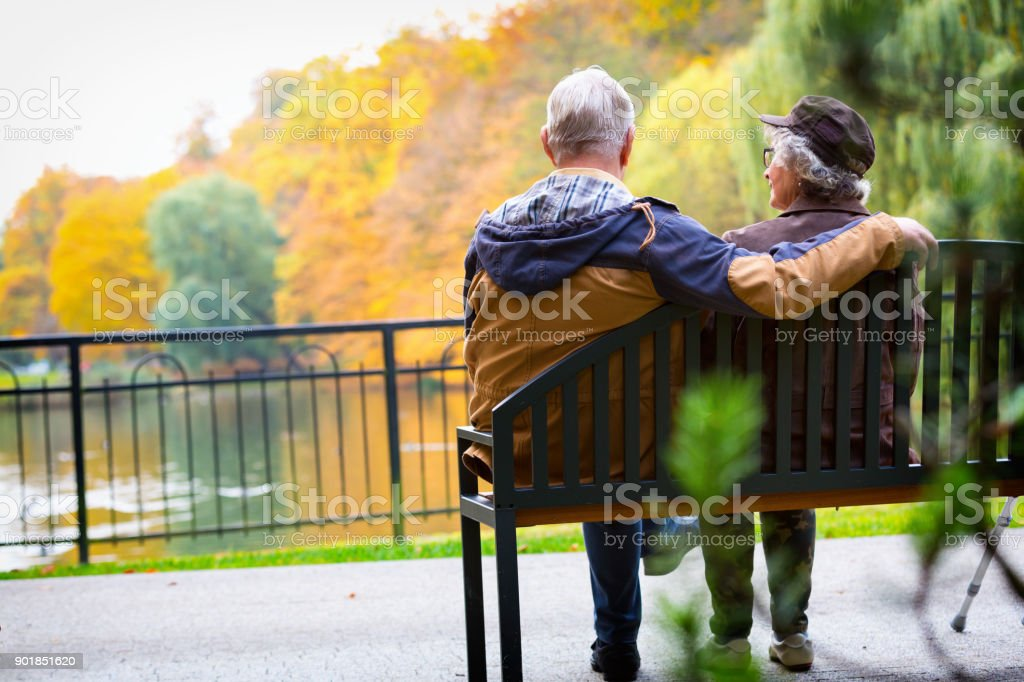 old couple sitting on a bench stock photo