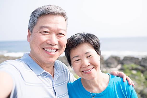 altes paar lächeln für sie - senior bilder wasser stock-fotos und bilder