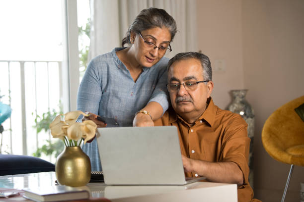 Old couple using laptop and credit card at home stock photo