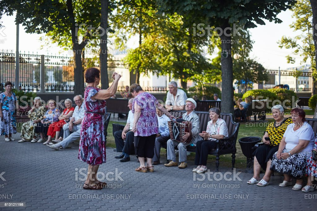 Group of happy seniors having fun together dancing in the park with...