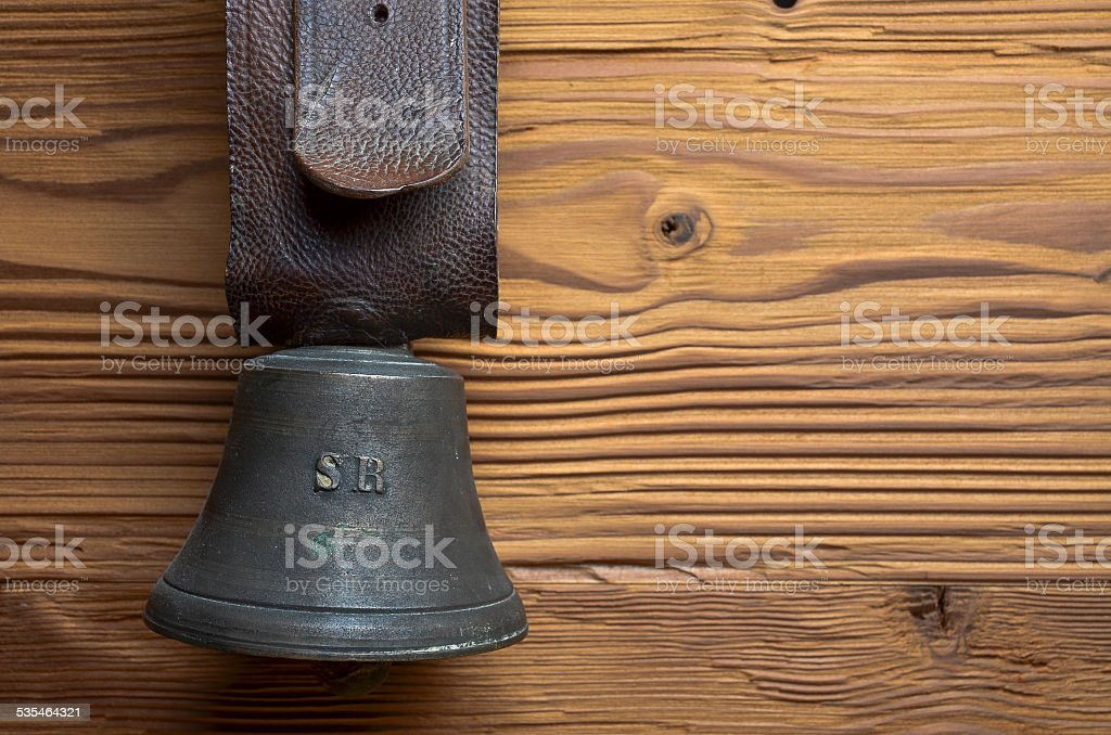 old cowbell with leather strap on pine wood stock photo