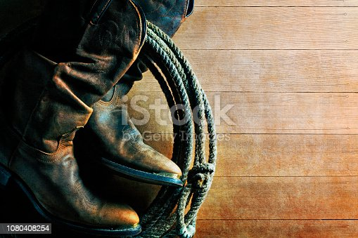 An old pair of cowboy boots and a lasso hang against a weathered wood plank wall.