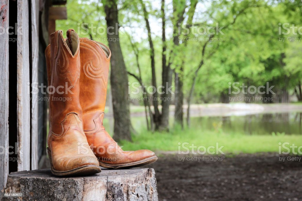 Old cowboy boots on a chopping block stock photo