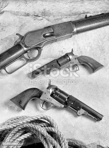 Old western cowboy rifle and pistols in black and white.