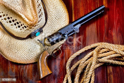 Old cowboy pistol ,straw hat and rope.