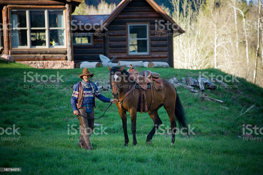 Old cowboy with horse in front of cabin stock photo