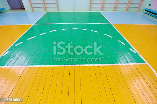 Old cracked floor of the sports hall with markings for basketball.