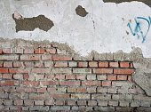 old cracked plaster in the brick wall