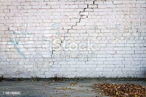 Old cracked white brick wall and ground