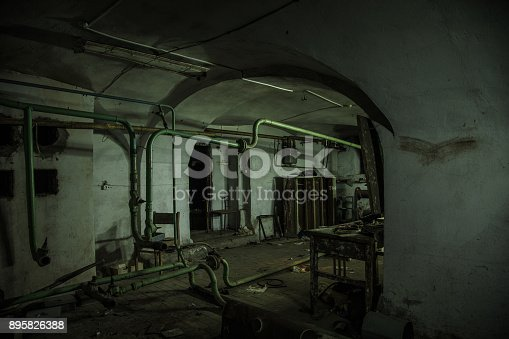 Old creepy cellar of abandoned asylum. Old rotten boiler, heating pipes.