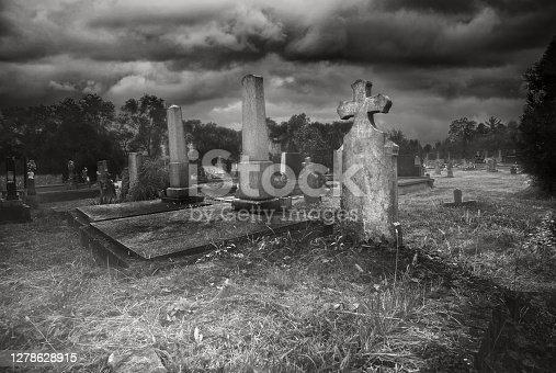 Old creepy haunted cemetery on foggy night.