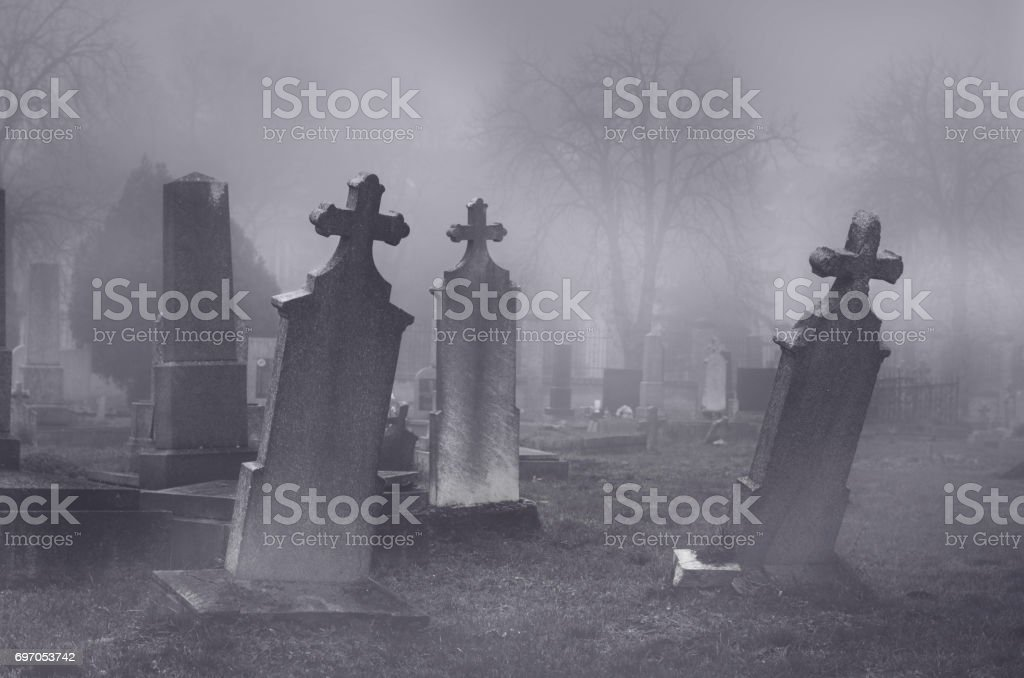 Old creepy haunted cemetery on foggy night Old creepy haunted cemetery on misty night. Autumn Stock Photo