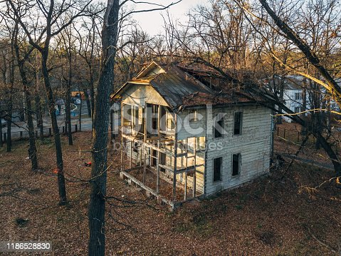 Old creepy wooden abandoned haunted mansion, aerial view.