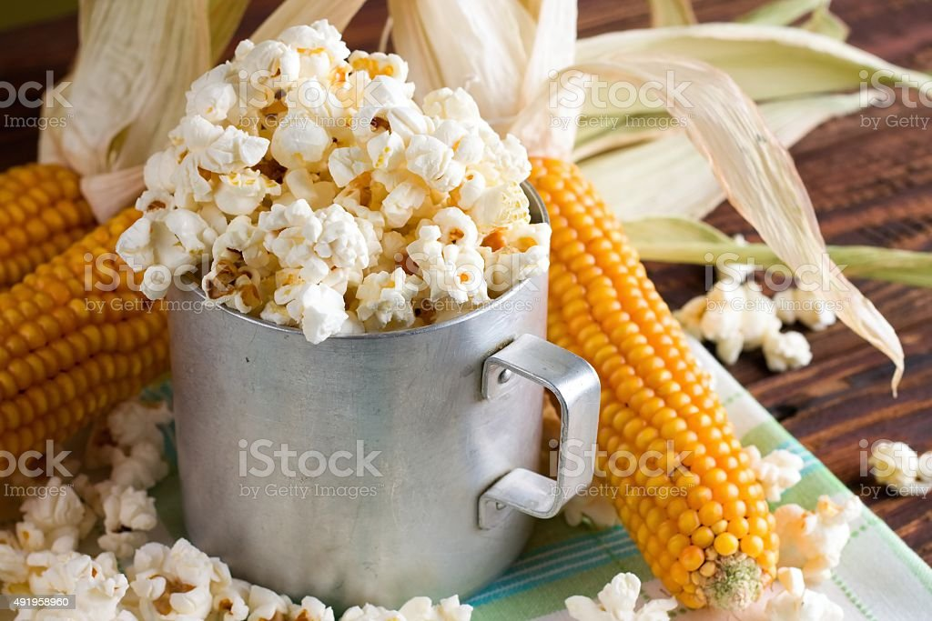 Old cup with popcorn and few corncobs stock photo