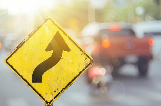 Antigua señal de advertencia de carretera curva en la carretera de tráfico borroso con colorido fondo abstracto de luz bokeh. Copiar el espacio de transporte y el concepto de viaje. Estilo de color de filtro de tono retro. - foto de stock