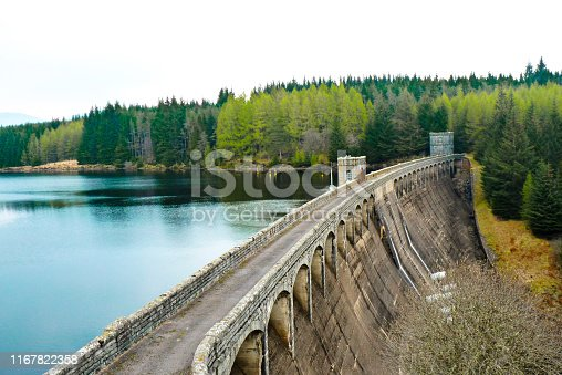 Old dam made in concrete with full lake and pine forest behind, Scotland, UK