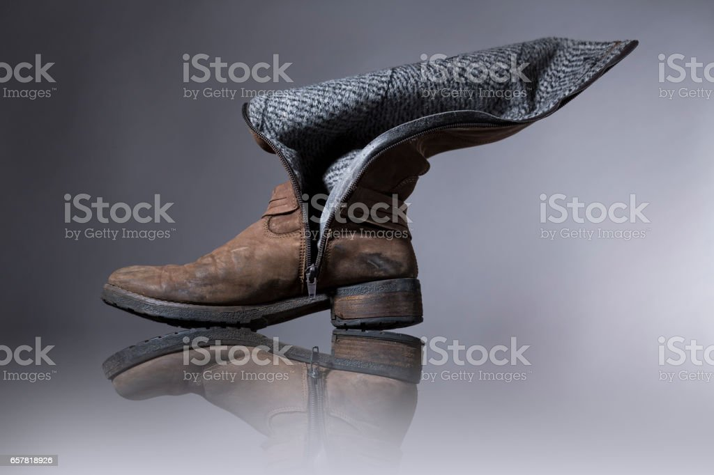 old, damaged female boots with gray background stock photo
