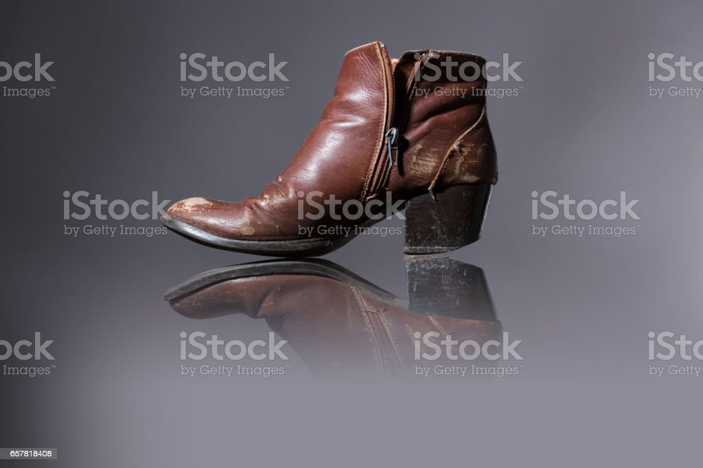 old, damaged female shoes with gray background stock photo