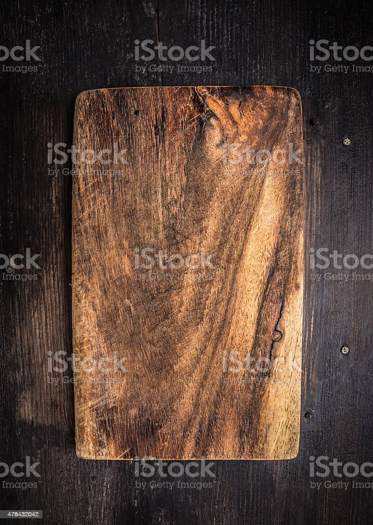 Old dark cutting board on brown wooden table, background stock photo